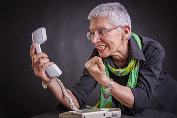 Angry, enraged senior woman yelling at a landline office phone, unhappy with customer service provided by the agent on the other side