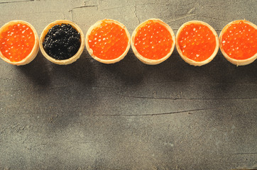 Black and red caviar tartlets frame, appetizer canapes on gray background, top view, toned
