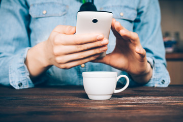 Woman in a denim shirt drinks coffee and uses a mobile phone