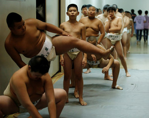 Elementary school sumo wrestlers stretch out as they wait to enter for their competitions during the Wanpaku sumo-wrestling tournament in Tokyo