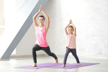 Mother and daughter doing exercise indoors