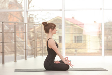 Young woman practicing yoga against window