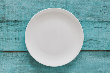Empty white plate on blue wooden background. Top view with copy space. Flat lay.