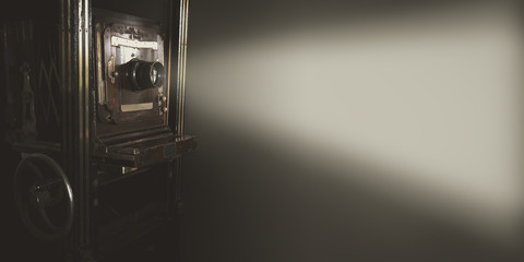 Vintage movie projector with light on gray backdrop use for background or web banner design.