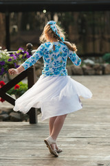 Cute little girl in white developing skirt dancing with outstretched arms outdoors. Adorable girl whirl on wooden platform. Beautiful warm summer day