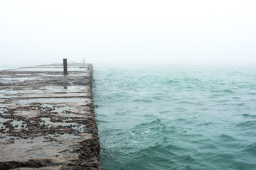 Old pier on the beach in winter