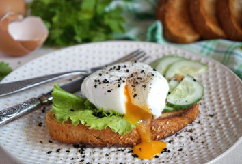 Egg poached on toast with lettuce and cucumber