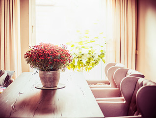 Beautiful living room with Chrysanthemums flowers bunch on dinner table at window  background. Autumn home decoration
