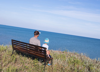 Father with child looking to the sea in front of the beautiful ocean and sky view.