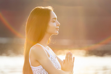 Portrait of beautiful young woman doing yoga in nature in summer sunrise. Relaxing, meditating, feeling alive, breathing, freedom and calm concept, copy space