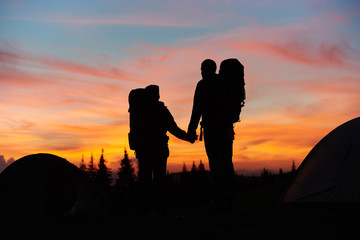 Silhouettes of a loving couple holding hands standing on top of the mountain while hiking together with their backpacks enjoying beautiful sunset with fiery colorful sky love relationships nature.