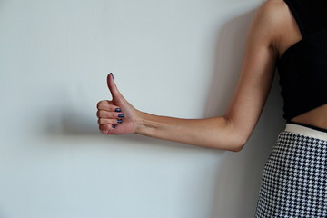Young woman's hand shows thumbs up. Gesture.