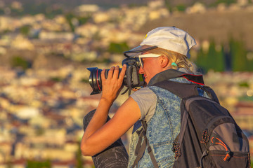 Nature woman photographer with camera takes picture outdoor. Profile of caucasian female with backpack shooting during a trekking.Professional photographer takes photo after hiking. Blurred background