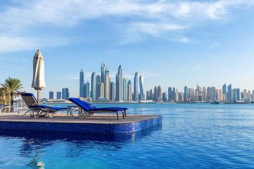 Skyline von Dubai mit Liegestühlen im Vordergrund zum Ausruhen