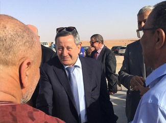Sonatrach's CEO Abdelmoumen Ould Kaddour (C) talks to employees during his visit at a gas site in Hassi R'mel