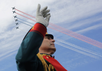 A member of a military band performs as Russian fighter jets fly in formation during the Navy Day parade in Kronshtadt, a seaport town in the suburb of St. Petersburg