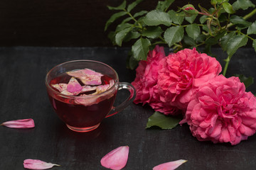 tea with petals of roses on a dark background