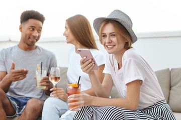 Friendly youngsters relaxing at restaurant, drinking cocktails or wine, communicating with each other. Cute woman in hat drinking mixed drinking typing message to her lover having joy while resting
