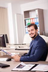 Portrait of Businessman in suit working in his office. Business and corporate. Image of young succesful entrepreneur at his work place.