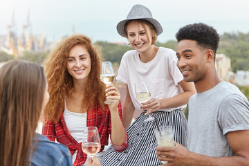 Group of happy friends wearing stylish clothing celebrating college graduation, drinking champagne and making toasts while partying on rooftop on summer sunny day. Fun, celebration and party