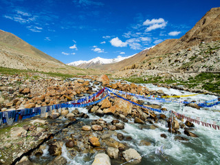 Buddhist prayer flags over the small river with blue sky and mountain on background in india