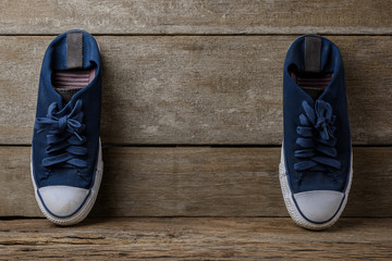 Blue canvas shoes on wooden background with copy space.
