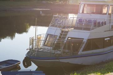 речной корабль у берега на закате солнца