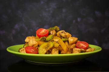 Stir fry chicken, zucchini and broccoli on dark background