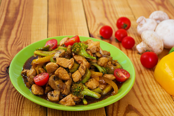 Stir fry chicken, zucchini and broccoli on wooden background