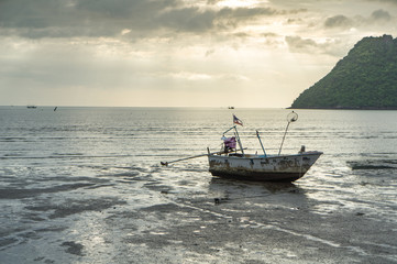 fishing boat on the beach with sea and sunrise background