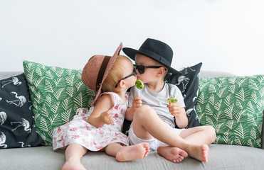 The kissing children in hats sit on a sofa.
