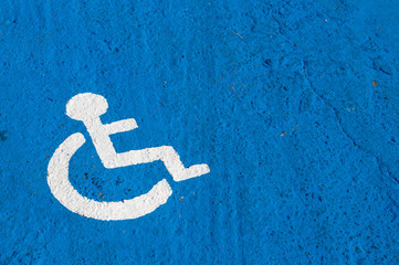 White disabled parking sign painted on blue background
