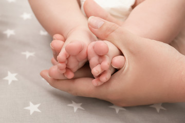 Mother hands holding little baby legs, closeup
