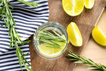 Glass of fresh lemonade with rosemary on table
