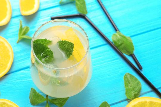Glass of fresh lemonade on color background