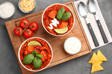 Two bowls with delicious chili turkey on wooden board