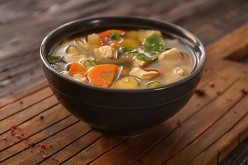 Bowl with delicious turkey soup on wooden board