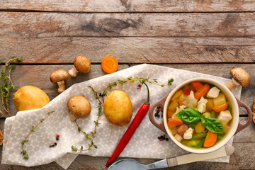 Casserole with delicious turkey soup on wooden background