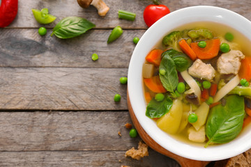 Bowl with delicious turkey soup on wooden background