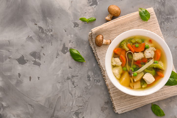 Bowl with delicious turkey soup on grey background