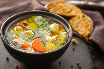 Bowl with delicious turkey soup on slate plate