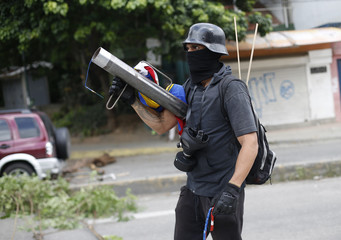 A member of the opposition holds a makeshift weapon as he mans a road block during the Constituent Assembly election in Caracas