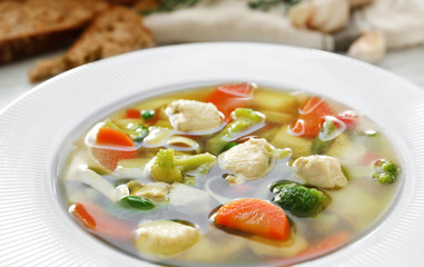 Plate with delicious turkey soup on table