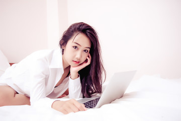 Beauty portrait of women  on the bed while learning with a laptop computer.