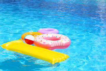 Inflatable mattress, donut and rings in blue swimming pool