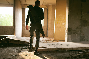 Athletic man walks through the ruins, with a cover for a gun for weeping, warm rays of light in the window