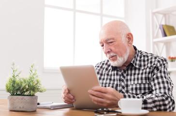 Senior man reading news on digital tablet