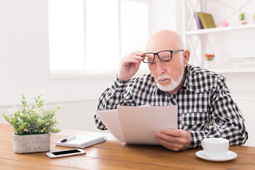 Shocked senior man looking at bills copy space