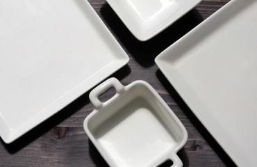 White square plates oriented diagonally on a black table