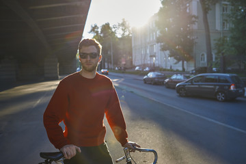 Summer urban shot of handsome bearded hipster in shades standing in the middle of deserted street with bicycle, waiting for his friend to join him for morning bike ride, sun shining in background